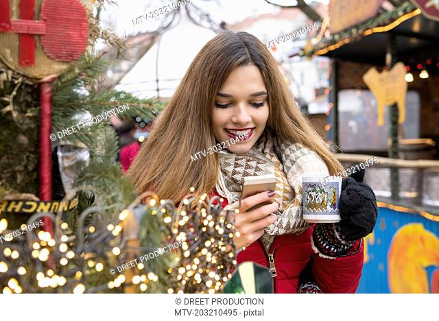 Young woman holding cup and using mobile phone
