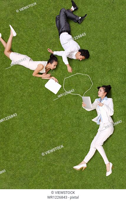 Young people lying on grass using tablet
