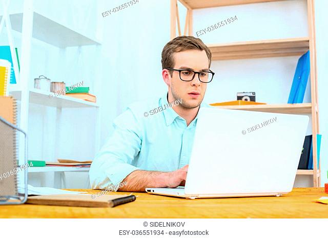 IT company. Young programmer working with laptop. Nice office interior. Professional coder looking at laptop