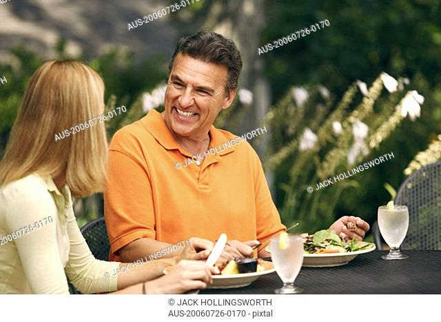 Mature man with a mid adult woman sitting at the table and smiling