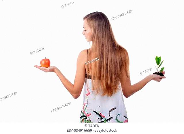 Beautiful young woman holding green sprout of tree and apple
