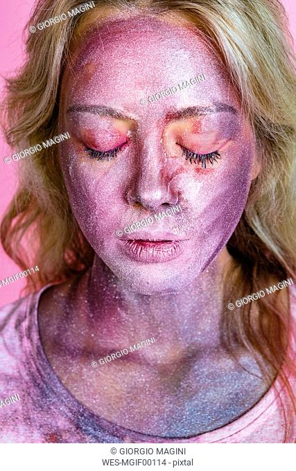 Portrait of young woman with metallic glimmer on her face in front of pink background