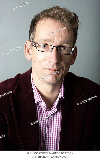 Tilburg, Netherlands. Studio-portrait of a long man with glasses