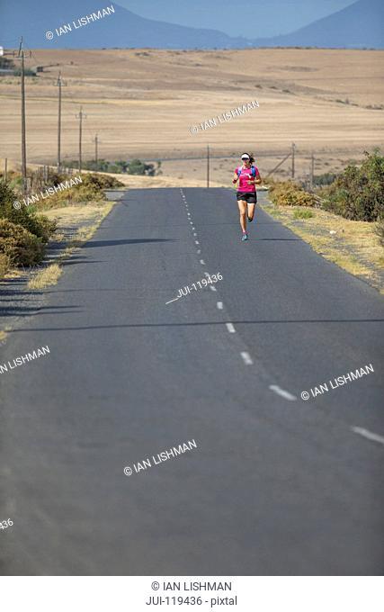 Female runner running on open road in arid landscape