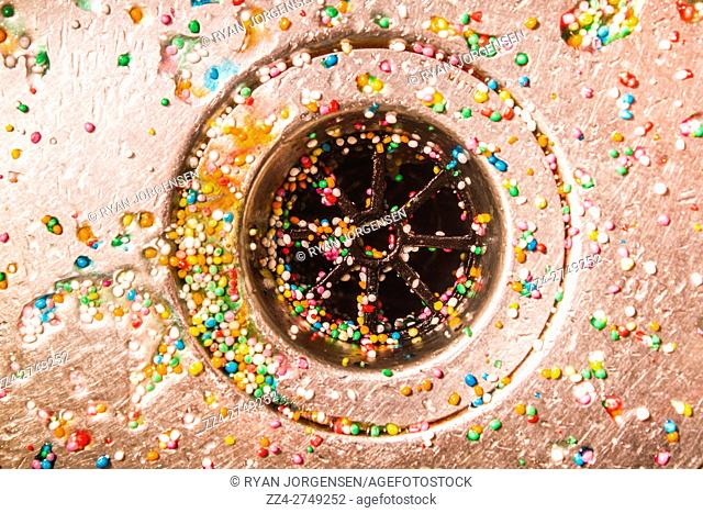 Scattered colorful sugar candy pearls or nonpareils lying in a silver stainless steel kitchen sink in and around the open plug hole and drain filter viewed from...