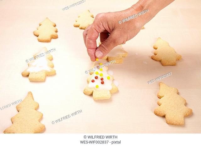 Woman putting nonpareils on Christmas tree cookies
