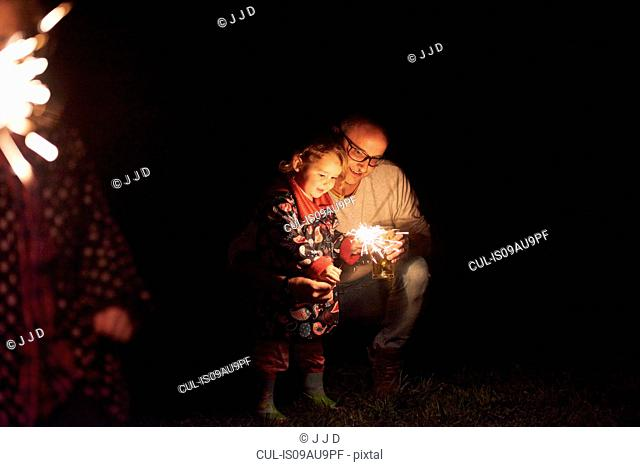 Father crouching next to daughter holding sparkler