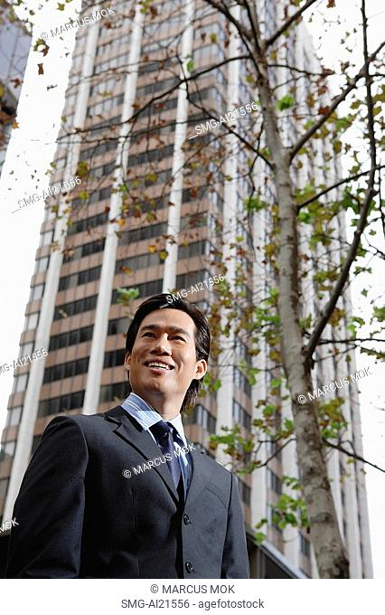 Businessman standing in the city, tree and building behind him