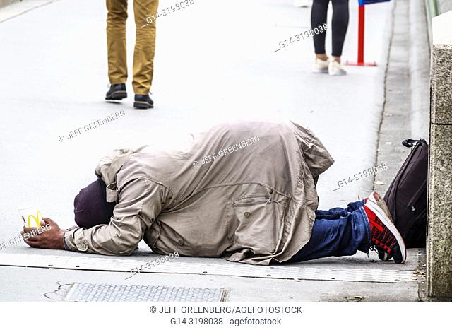 United Kingdom Great Britain England, London, Westminster Bridge, Thames River, Asian, man, prostrated on ground, holding McDonald's cup, begging, street beggar