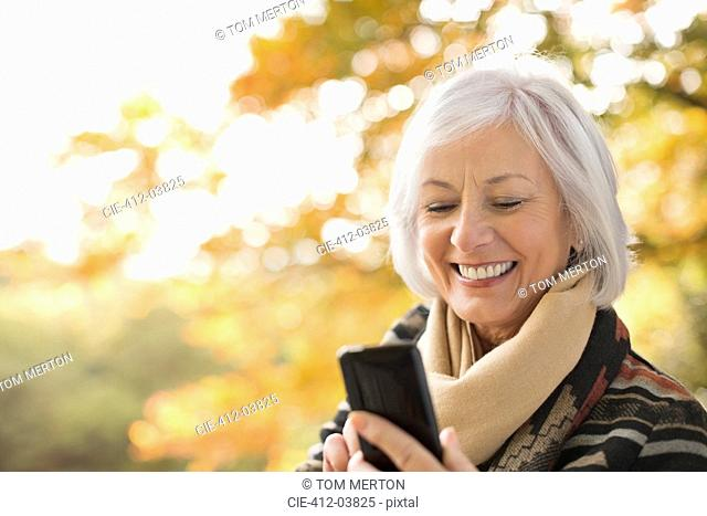 Older woman using cell phone in park