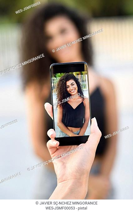 Woman taking photo of her friend with cell phone, close-up