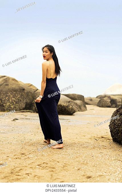 A model in formal dress walks barefoot on the sandy beach; Xiamen, China
