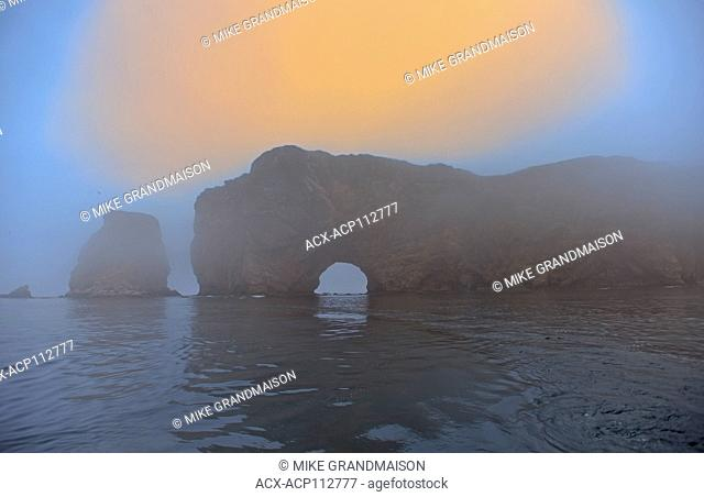 Roche Perce and Atlantic Ocean sin fog at sunrise on Gaspe Peninsula, Perce, Quebec, Canada