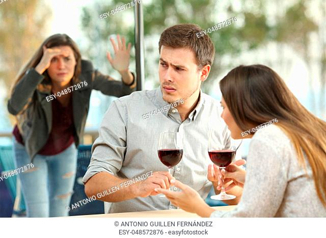 Obsessed ex girlfriend spying on an annoyed couple dating in a restaurant