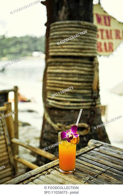 A glass of freshly squeezed orange juice with orchids on a beach Thailand