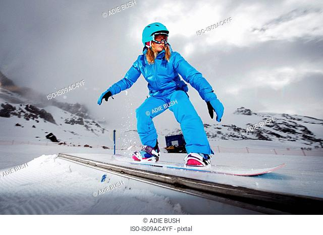 Female snowboarder at top of mountain