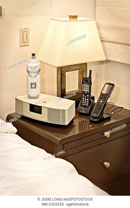 21st Century Bedside Night Table featuring clock radio, cordless phone, universal remote control, lamp and a water bottle. New York City