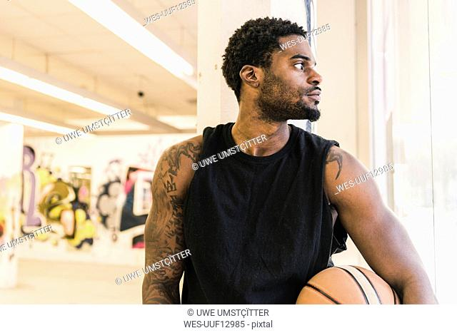 Man with tattoos holding basketball looking away