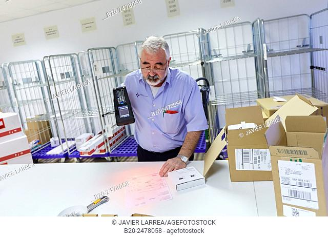 Man scanning materials with bar codes reader, Warehouse, Hospital Donostia, San Sebastian, Basque Country, Spain