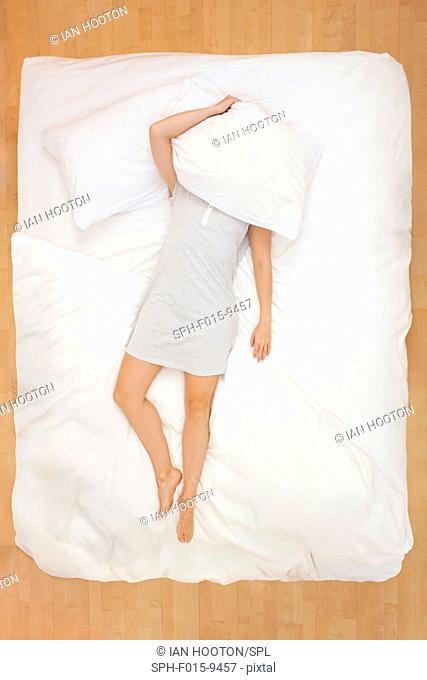 MODEL RELEASED. Mid adult woman lying in bed with pillow over head