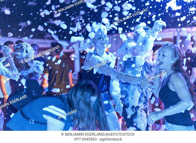 girls dancing together at foam party at music festival. German ethnicity. At holiday destination Hersonissos, Crete, Greece
