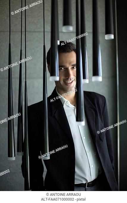 Smiling businessman standing behind pendant lights