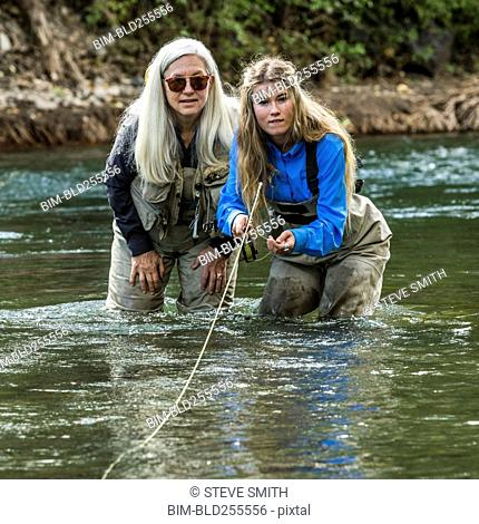 Caucasian mother and daughter fly fishing