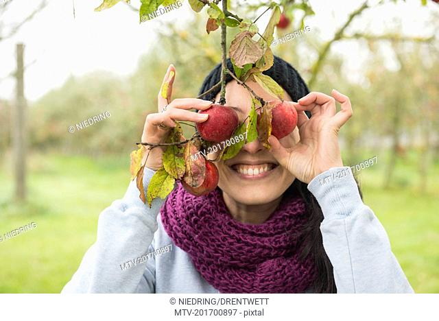 Woman holding apples in front of her eyes, Bavaria, Germany