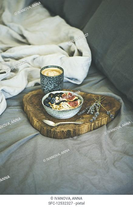 Rice coconut porridge with figs, berries and hazelnuts and cup of espresso over rustic wooden board background
