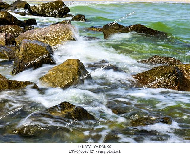 view of the Black Sea with large stones on a summer sunny day, the village of Iron Port Ukraine, long exposure
