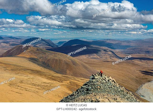 HIKER FOLLOWING THE ROCKY CREST OF MOUNT MALCHIN, TAVAN BOGD MASSIF IN THE BACKGROUND, ALTAI, BAYAN-OLGII PROVINCE, MONGOLIA