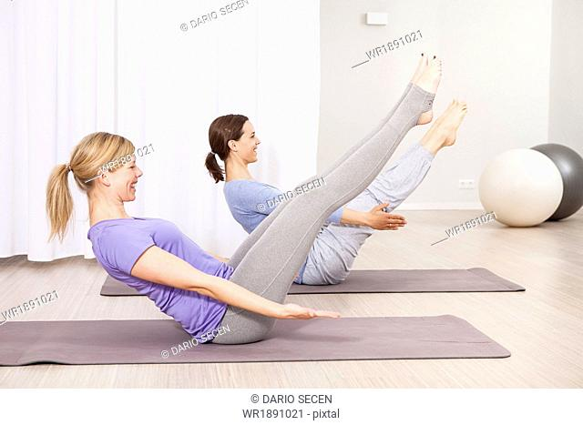 Two women doing Pilates exercise, feet outstretched