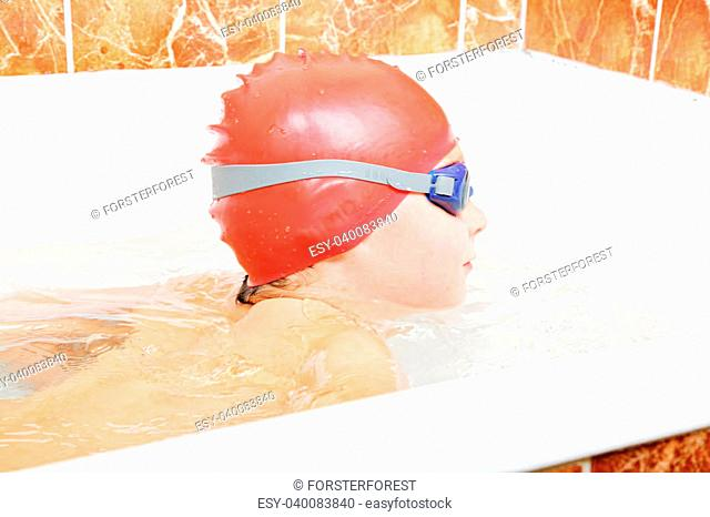 Little boy with goggles and cap breaststroke swimming in bathtub