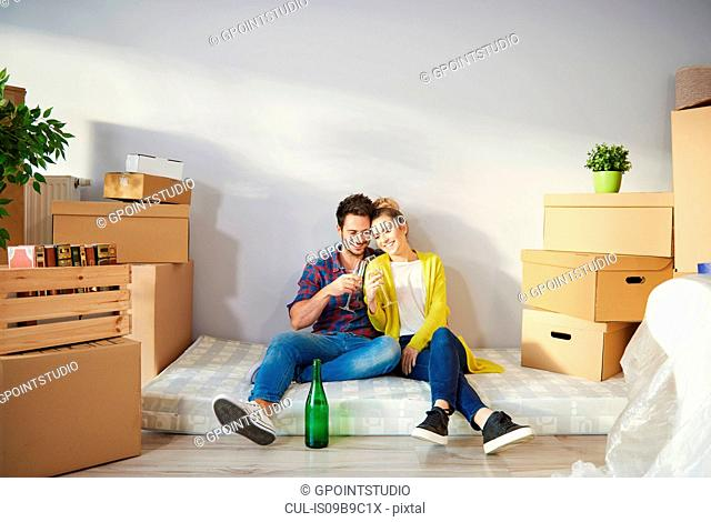 Young couple at home, surrounded by cardboard boxes, drinking champagne