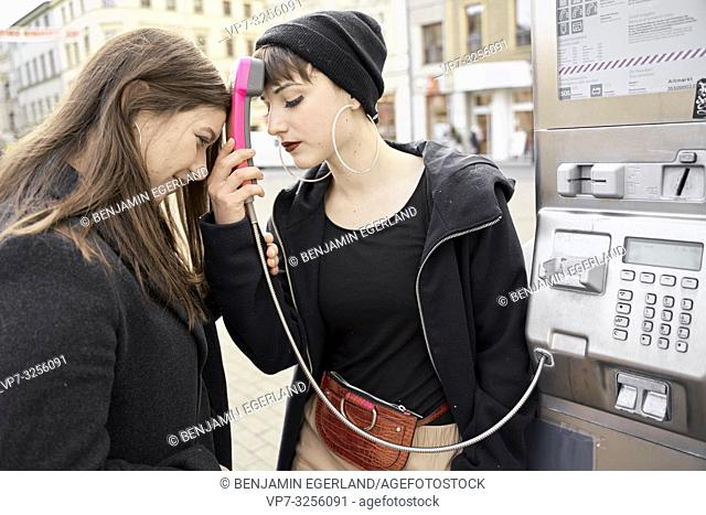 two women putting heads together with payphone, communication problems, waiting for call, in city Cottbus, Brandenburg, Germany