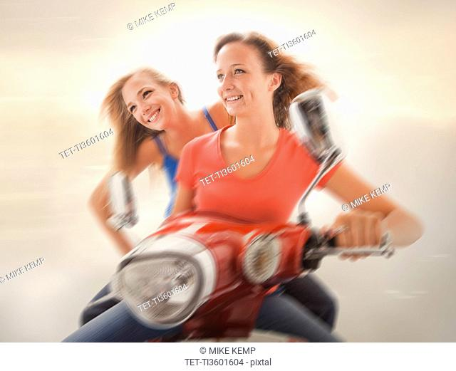 Young girls 16-17 riding scooter