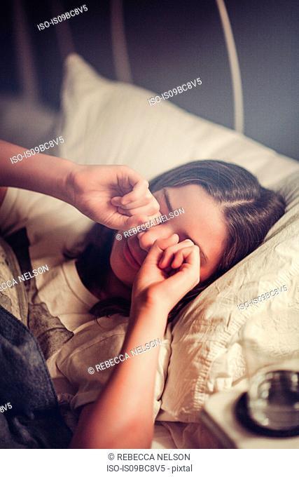 Girl rubbing eyes in bed