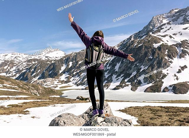 Spain, Asturias, Somiedo, woman standing with raised arms in mountains