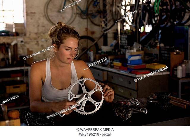 Female mechanic holding crankset and crank arm