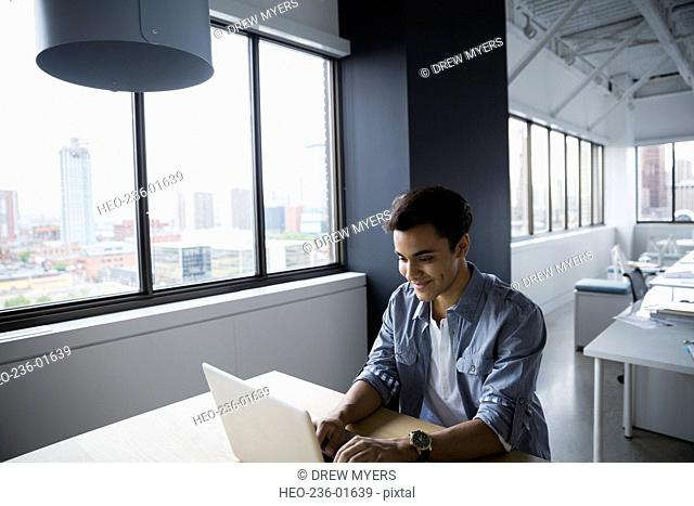 Businessman using laptop at table in office