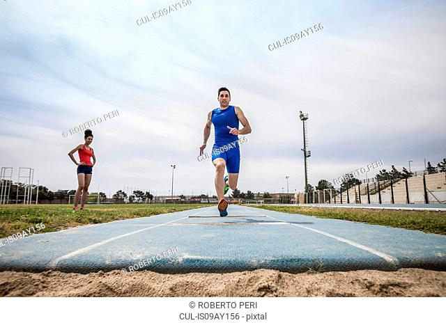 Young male long jumper sprint training at sport facility