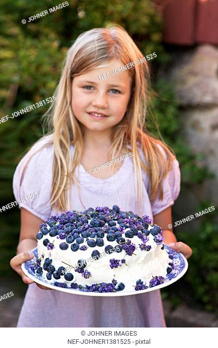 Blond hair girl holding blueberry cake