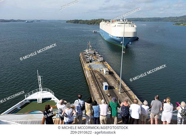 Tourists watch as a ship approaches a lock in the Panama Canal