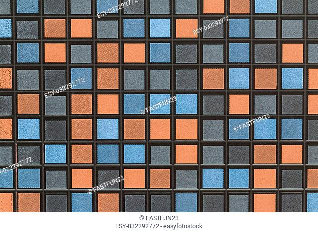 mosaic tile of a wall decorated with black blue gray and orange pattern tiles blackground