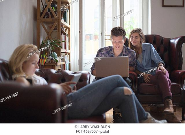 Woman with digital tablet while friends using laptop at home