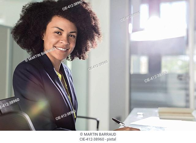 Portrait smiling, confident businesswoman working in sunny office