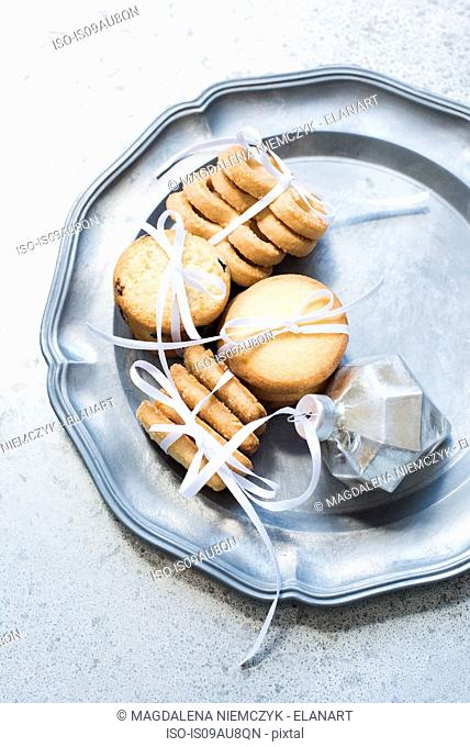 Overhead view of shortbread cookies tied with white ribbon on silver serving dish