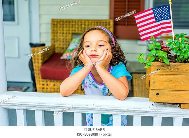 Bored girl waiting on porch on Independence Day