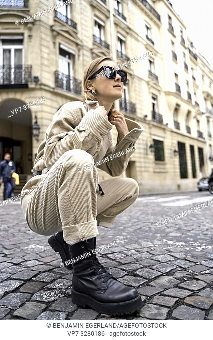 cool fashionable woman crouching at street during fashion week, in Paris, France