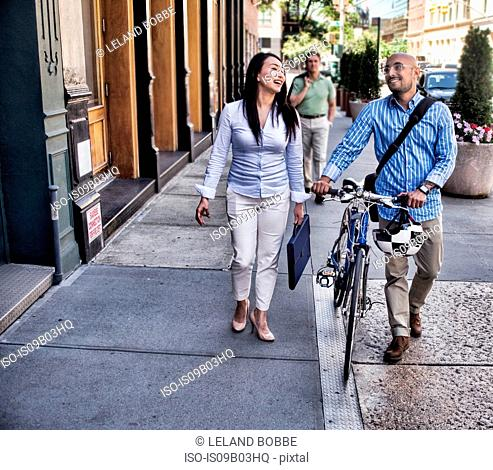 Business man and woman walking in street, man pushing bike, smiling